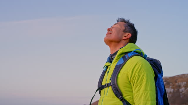 SLO MO Asian male hiker enjoying the nature on the mountain top at sunset