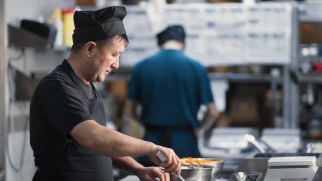 asian male kitchener mixing dish cooking food at cuisine. medium close up shot on 4k red camera - stołówka filmów i materiałów b-roll