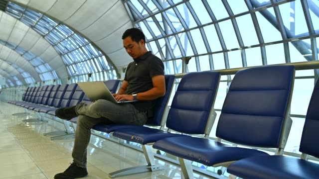 asian male working with laptop while waiting flight at international airport - fare una prenotazione video stock e b–roll
