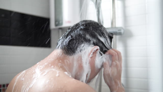 vídeos de stock e filmes b-roll de asian man are taking hair and body wash shower in bathroom. - tomar banho