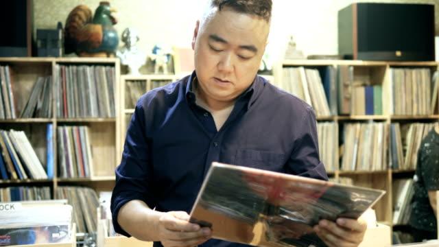 asiatischer mann in einem plattenladen - antique shop stock-videos und b-roll-filmmaterial
