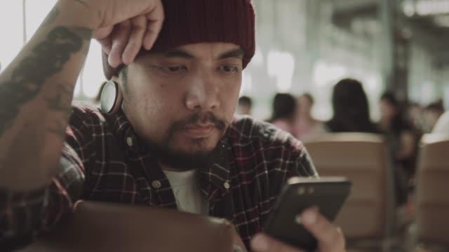 asiatiska man chattar på telefon i avgångshall - människokroppsdel bildbanksvideor och videomaterial från bakom kulisserna