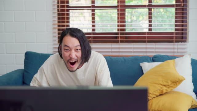アジア人男性が自宅のテレビリビングルームの前でサッカーの試合を応援し、男性はリビングルームのソファに横たわって幸せな気持ち。ライフスタイルの男は、自宅のコンセプトで朝にリ� - 応援点の映像素材/bロール
