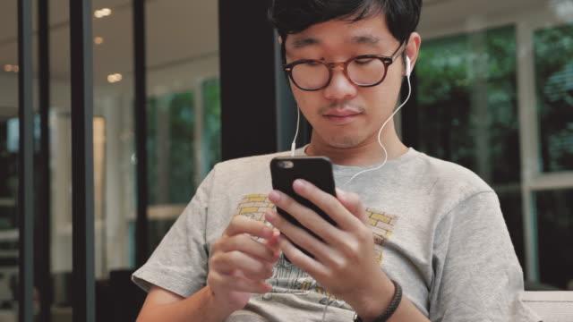 Asiatique homme choisissant et écoute de la musique sur téléphone intelligent, 4K - Vidéo