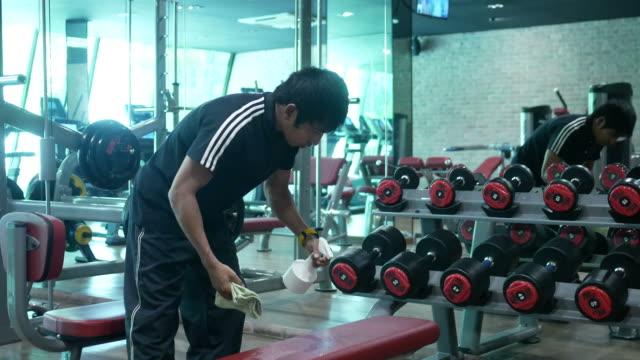아시아 남자 휘트니스에서 운동 장비를 청소 - 운동장비 스톡 비디오 및 b-롤 화면