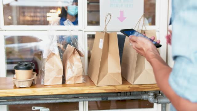 asian man customer pick up food from restaurant ist bestellung über smartphone, soziale abstand durch technologie während covid-19, neues kleines unternehmen und neues normales konzept - bucht stock-videos und b-roll-filmmaterial
