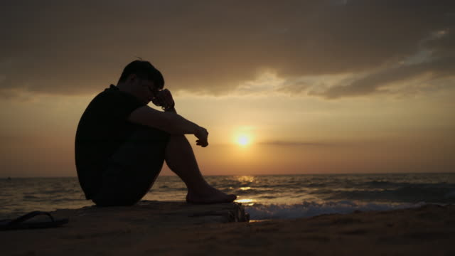Asian man depressing and sitting by the beach at sunset, Pattaya