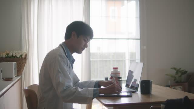 自宅で患者の話を聞いて遠隔医療を行うアジアの男性医師。 - パソコン 日本人点の映像素材/bロール