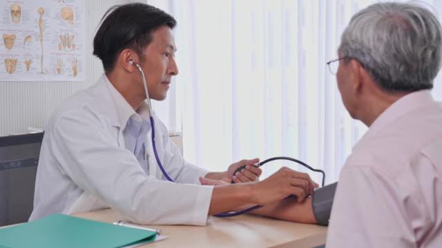 アジア人男性医師は、病院の診察室で高齢者患者に血圧を測定し、アジアのシニア男性は医療専門家による健康診断を受ける。 - 心臓点の映像素材/bロール