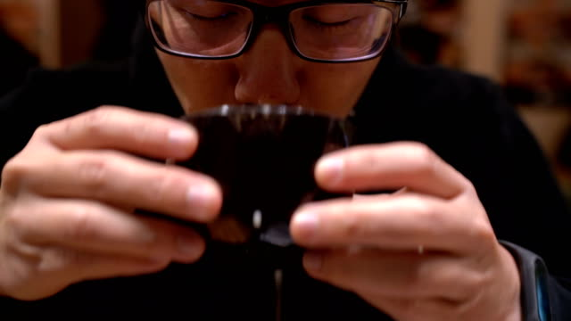 Asian man drinking soup in Japanese restaurant