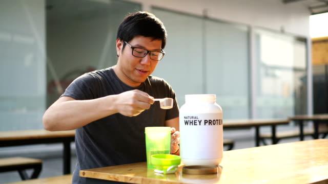 stockvideo's en b-roll-footage met aziatisch mens wei eiwit drankje drinken na de sportschool - talk