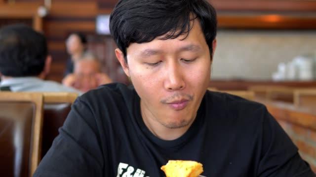 Asian man eating breakfast in restaurant.