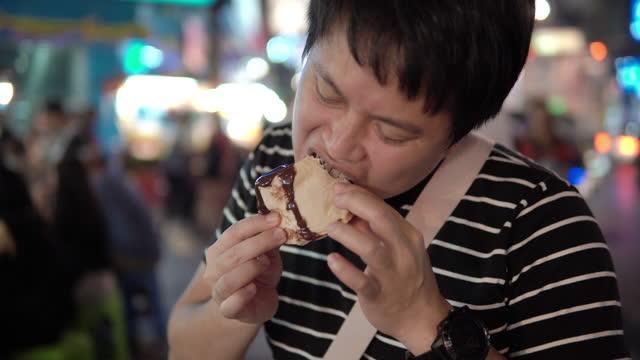 Asian man eating Chocolate Toast at Yaowarat Street Food Road, Bangkok, Thailand.
