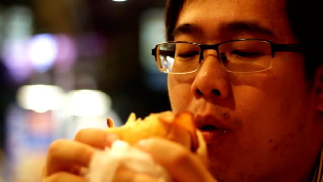asian man eating hamburger