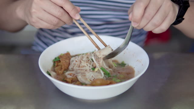 vídeos y material grabado en eventos de stock de hombre asiático comiendo fideos de cerdo tailandés con sopa. - comida china