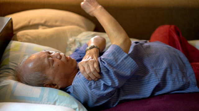 Asian man feeling pain of his arm muscle on bed at home