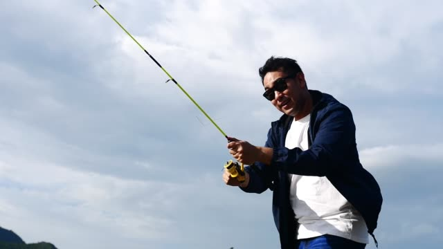 Asian man fishing with nature background, lifestyle concept.