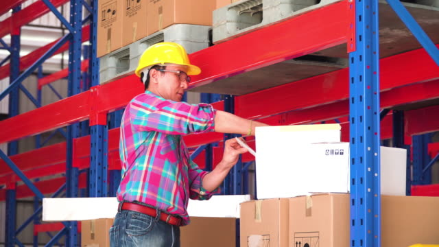 Asian man foreman looking at paperbox and check goods in box in warehouse