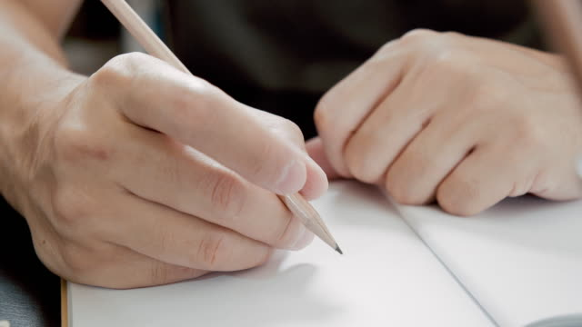 Asian man freelance writer is writing his article on a notebook.idea and inspiration concept.