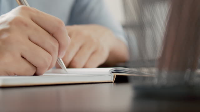 asian man frilansskribent skriver sin artikel på en anteckningsbok. idé-och inspirations koncept. - anteckningsblock bildbanksvideor och videomaterial från bakom kulisserna