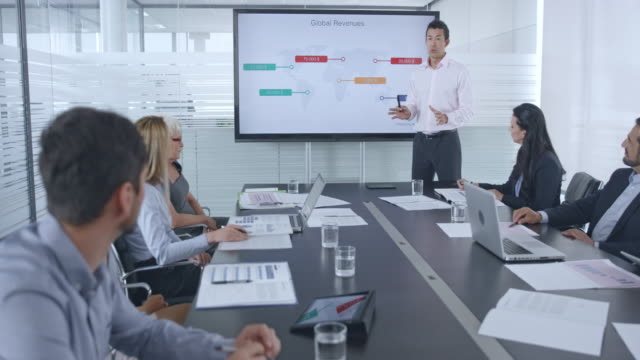 Asian man giving a financial presentation to his colleagues in the conference room video