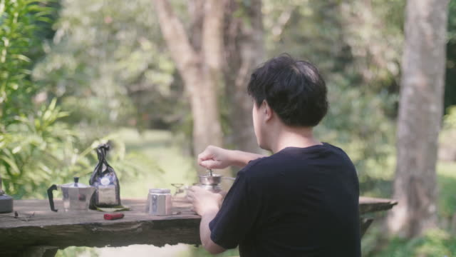 Asian man Grinding coffee beans with an hand coffee grinder and relaxing in beautiful day.
