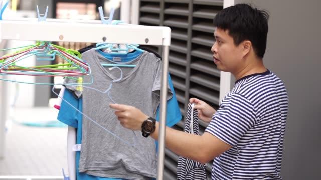 アジア男は、太陽の下で洗濯後洗濯物を乾燥させるシャツをぶら下げします。 - 楽しい 洗濯点の映像素材/bロール