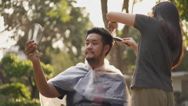 Asian man holding mirror getting hair cut by his couple at home in covid-19 corona virus situation