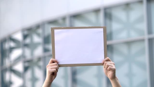 asiatischer mann hält weißbuch über den kopf - poster stock-videos und b-roll-filmmaterial