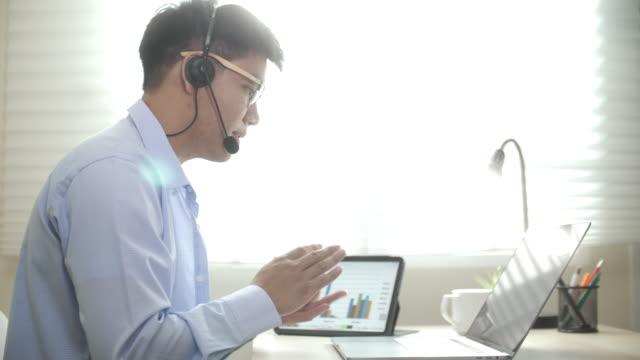 青いカジュアルシャツを着たアジア人男性が自宅でラップトップでビデオ会議を開き、自宅で働き、リモートで働いています - オンライン会議点の映像素材/bロール