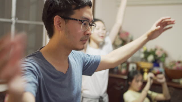 4K CU Asian man in eyeglasses dancing exericse at home with his family