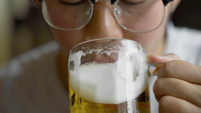 眼鏡をかけたアジア人男性ビールを飲む - ビール点の映像素材/bロール