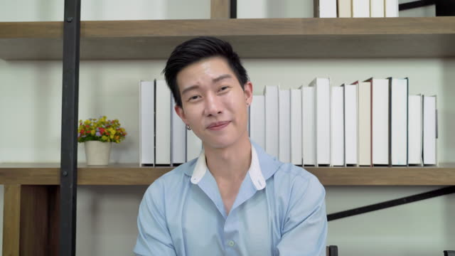 Asian man is greeting through video calls, he is with friends online via social media.