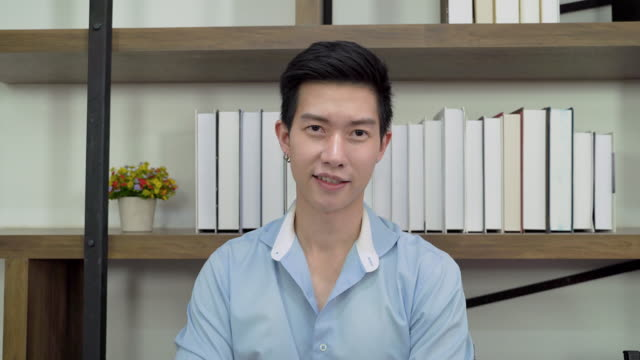 Asian man is greeting through video calls, he is with friends online via social media and sat and listened intently.
