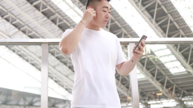 a asian man is using wireless headphones - auricolari wireless video stock e b–roll