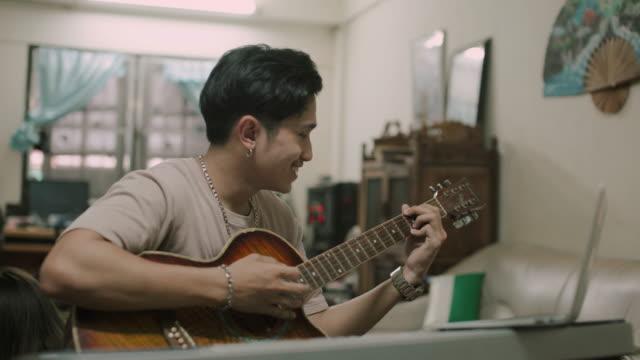 asiatiska man lära sig att spela gitarr hemma lager video - akustisk gitarr bildbanksvideor och videomaterial från bakom kulisserna