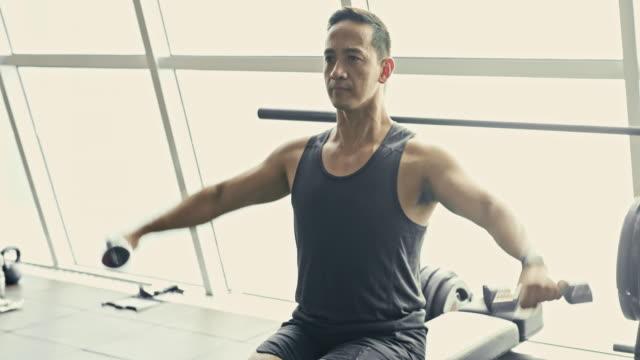 asian man lifting dumbbells at gym - филиппинского происхождения стоковые видео и кадры b-roll