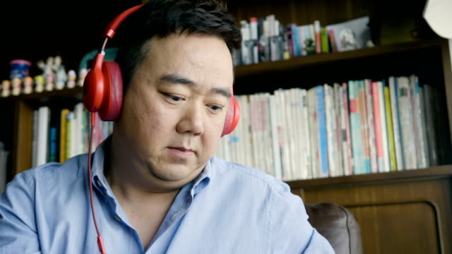 Asian man listening music at home