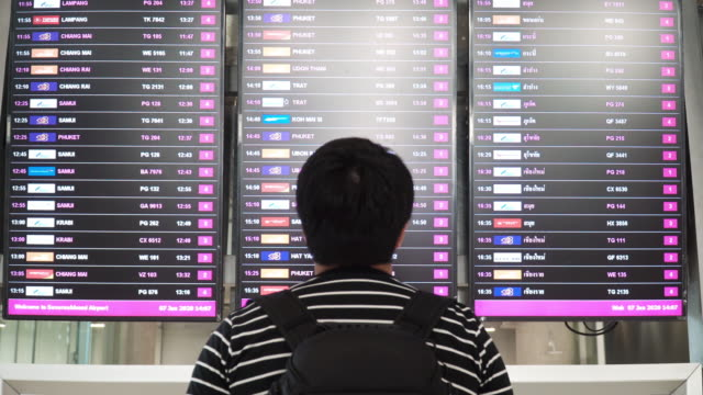 Asian Man looking for gate from arrival departure board in airport.