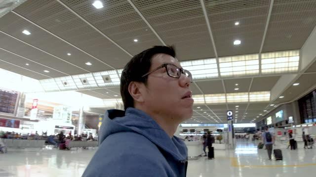 アジア人男性は空港で失われました。 - 方向点の映像素材/bロール
