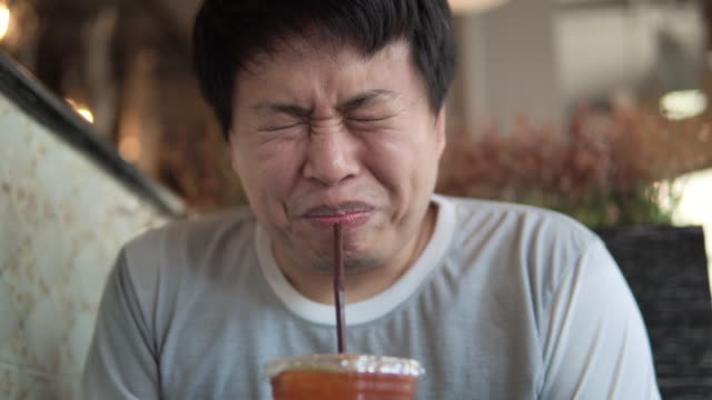 asian man makes faces grimacing when eating lemon tea. - gusto aspro video stock e b–roll