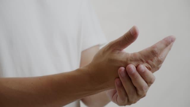 vídeos de stock, filmes e b-roll de massagem homem asiático em sua dor de mão - punho