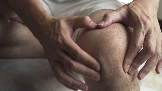 vídeos de stock, filmes e b-roll de massagem asiática do homem em sua dor do joelho e sentimento mau - articulação humana