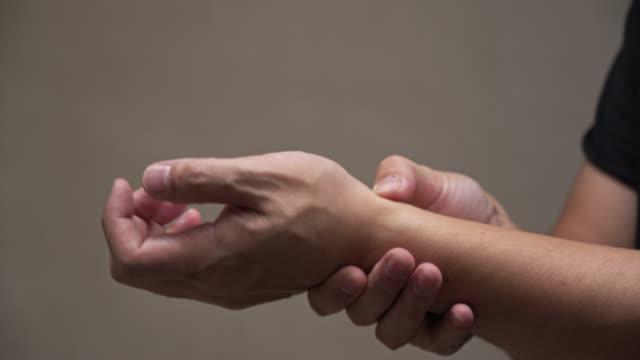 vídeos de stock, filmes e b-roll de massagem homem asiático em sua dor de pulso mão - punho