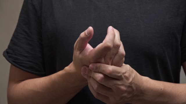 asian man on black shirt feel pain on his finger.muscle pain, health care concept.