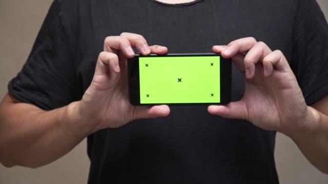 vídeos de stock e filmes b-roll de asian man on black t-shirt holding smartphone with green screen.technology and communication concept - teeshirt template