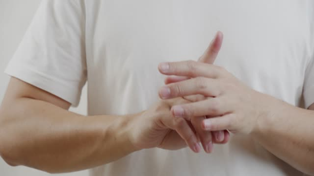 asian man on white shirt feel pain on his finger.muscle pain, health care concept.