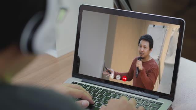 stockvideo's en b-roll-footage met aziatische mens online het leren conferentie met instructeur via laptop - luidspreker