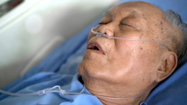 Asian man patient sleeping in hospital with oxygen tube 4K CU Asian man patient sleeping in hospital with oxygen tube medical oxygen equipment stock videos & royalty-free footage