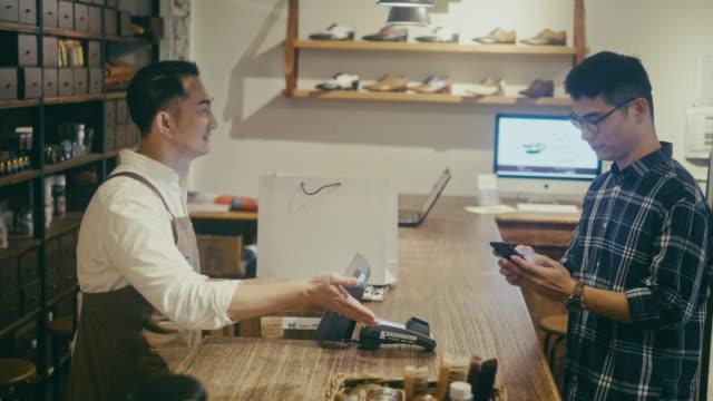 アジアの男性は、メンズブティックでモバイルで支払う(スローモーション) - 小売り点の映像素材/bロール